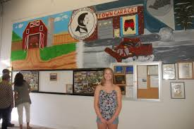 masuk student creates town mural monroe courier victoria yencik stands below the mural she painted in one of the highway department s garages