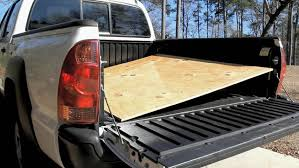 bed of truck sheet of plywood pulled part of the way off of a pickup truck bed