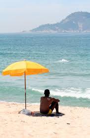 Beach Sun Umbrella File Man Sitting Under Beach Umbrella Jpg Wikimedia Commons