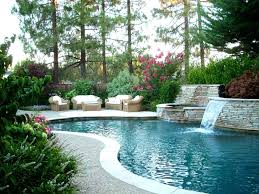 swiming pools wooden outdoor sofas with mini waterfall also forest