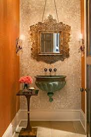 half bath design with hanging ornate mirror and wall sconces and