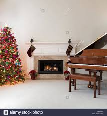 living room with glowing fireplace grand piano and decorated