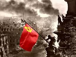 Un soldado soviético coloca la bandera roja sobre la cúpula del Parlamento alemán el 9 de Mayo de 1945