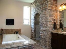 gorgeous bathroom with rustic stone wall and shower area for