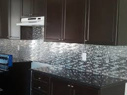 gray small tile back splash with dark brown wooden cabinet and