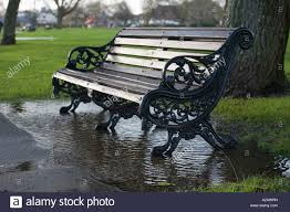 a park bench on a rainy day stock photo royalty free image