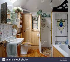stained glass panel behind bath in cottage bathroom with walk in