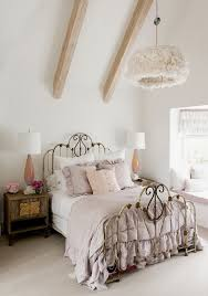 wooden beam ceiling and ornate black metal bed frame for shabby
