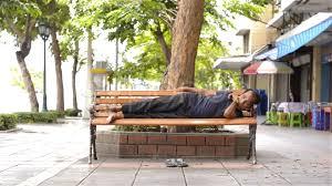 video homeless man sleeping on bench on sidewalk 11202629