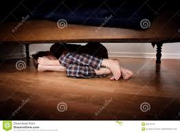 fearful boy hiding under the bed stock photo image 85214244