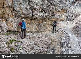 narrow picture ledge climbers walking on narrow ledge protected by via ferrata set