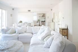 white slipcover sofa with dark wood floor beige fireplace bay window