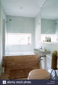 shower above wood paneled bath in modern white bathroom with large