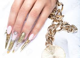 beautiful long nails in a gold design with rhinestones nail
