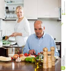 elderly senior with mature wife doing home chores stock photo