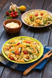 pasta salad with mayo two plates of vegetarian pasta salad made of tricolor fusilli