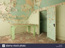 a table sitting in a room with peeling paint in an abandoned stock