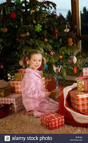 smiling holding card near christmas tree and gifts stock
