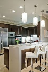 modern kitchen look light wood white range hood wood cabinets marble island top and