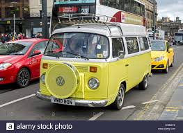 yellow type 2 classic vw camper van driving along princes street