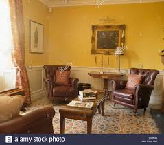 french country livingroom brown leather armchairs and patterned tiled floor in yellow french