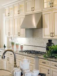 antique white kitchen cabinets with subway tile backsplash antique white kitchen with wood floors and an island sink