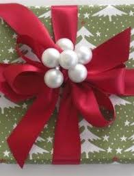 christmas wrapping bow stack 3 gifts wrapped in coordinating paper tie a bow around the
