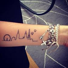 little forearm tattoo of the skyline of paris and london on dani