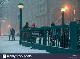 entrance to a new york city subway station during a winter blizzard