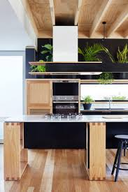 a turn of the century victorian gets a modern extension design milk instead of a traditional backsplash a long window was installed helping to keep the kitchen light above that a shelf holds a collection of potted plants