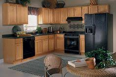 kitchens with oak cabinets with black appliances and granite