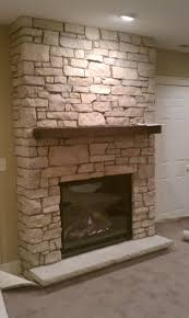 interior grey stone fireplace with brown wooden board mantel and