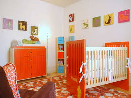 nursery room with animal wall decor and orange accents choosing