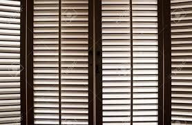 wooden shutters in front of bright sunlit windows stock photo