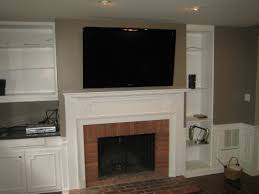 fireplace mounting tv above fireplace with shelving unit design