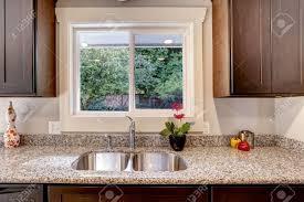 cuisine avec fenetre armoire brun foncé de cuisine avec évier et comptoir de granit vue