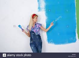 happy smiling woman painting interior white wall in blue and green
