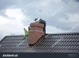 worker on roof repairs brick chimney stock photo 382360393