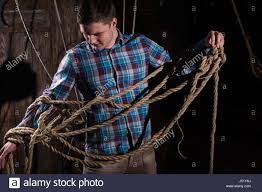 young man freed from captivity and selecting from ropes escape