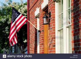 Brick Homes by An American Flag Hangs From A Front Porch In A Neighborhood Of