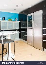large stainless steel fridge freezer on black wall of modern stock