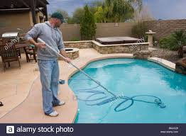 man cleaning and vacuuming swimming pool stock photo royalty free