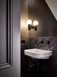 Modern Powder Room - small black powder room features a white porcelain sink mounted on