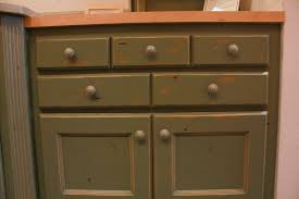 affordable custom cabinets showroom kitchen traditional style knotty alder green painted with sand through and distress recessed panel doors 2