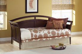 dark brown wooden trundle bed with brown pattern pillows and white