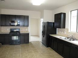marble countertops white kitchen cabinets with black appliances