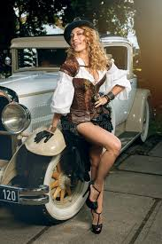 woman dressed in steampunk style posing over retro car stock photo
