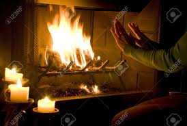 a woman warming her hands by a roaring fire with candles lit