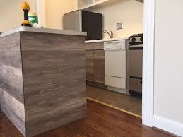 reface kitchen cabinet how to reface kitchen cabinets using vinyl flooring curbly