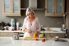 femme plus cuisine femme plus âgée heureuse dans la cuisine coupant les légumes frais
